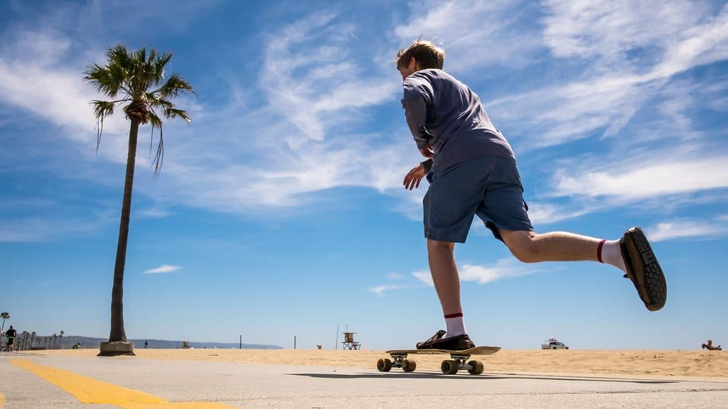 young guy on a skateboard by the beach